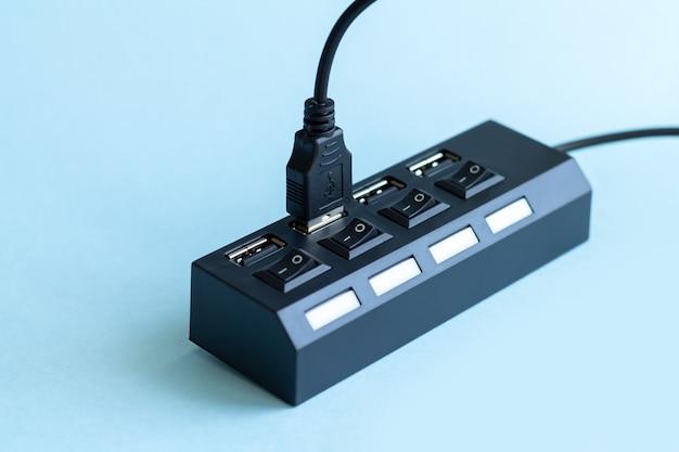 Zwarte usb-hub met usb-kabelstekker op lichtblauw oppervlak