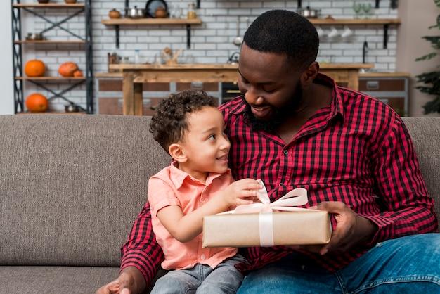 Zwarte vader die giftdoos geeft aan zoon