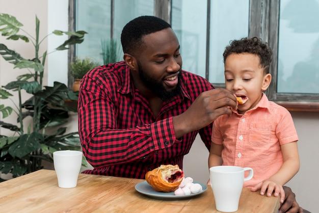 Zwarte vader die kleine zoon met croissant voedt