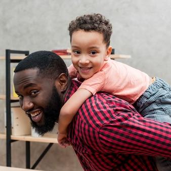 Zwarte vader die zoon op rug vervoert