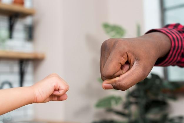 Zwarte vader en kleine zoon stoten vuisten