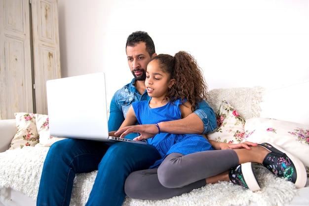 Zwarte vader en zijn dochter die op een laag met laptop situeren