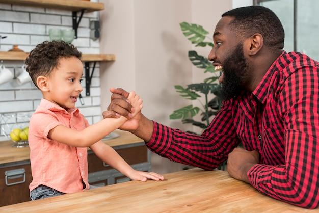 Zwarte vader en zoon arm worstelen