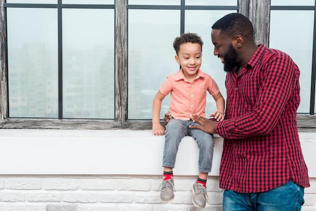 Zwarte vader en zoon die bij vensterbank spreken