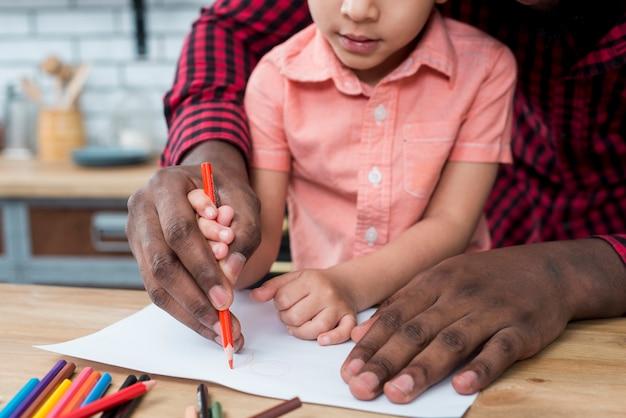 Zwarte vader en zoon die op papier trekken