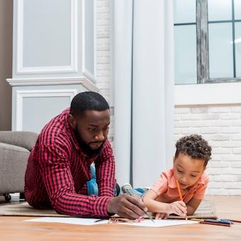 Zwarte vader en zoon die op vloer trekken
