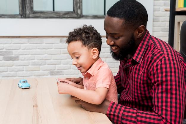 Zwarte vader en zoon die tablet gebruiken