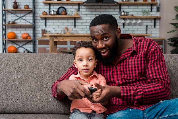 Zwarte vader en zoon die tv kijken