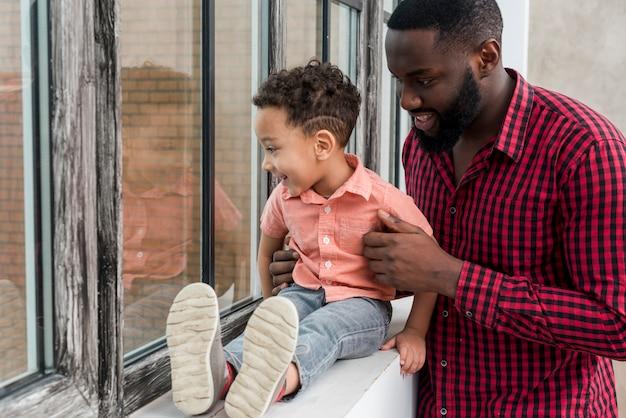 Zwarte vader en zoon die venster bekijken
