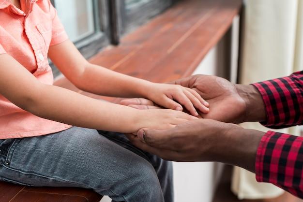 Zwarte vader en zoon hand in hand