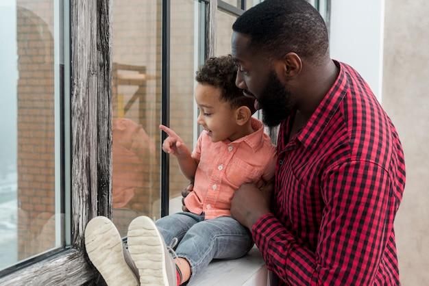 Zwarte vader en zoon kijken naar venster en weg wijzen