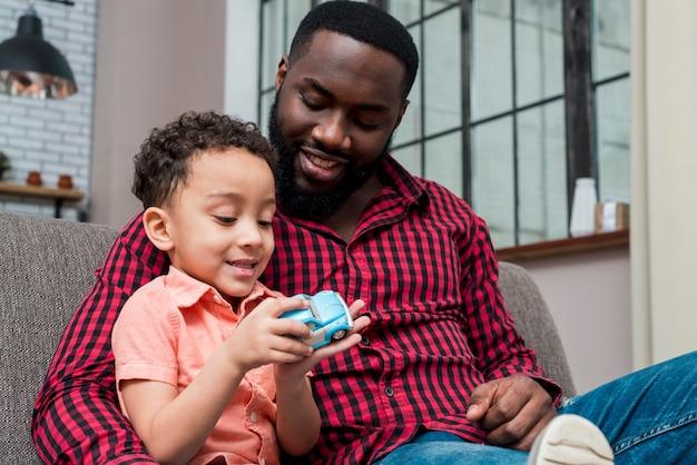 Zwarte vader en zoon spelen met blauwe speelgoedauto
