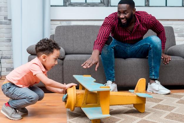 Zwarte vader en zoon spelen met grote speelgoedvliegtuig