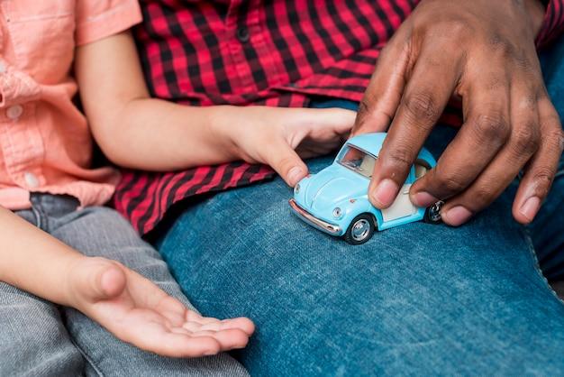 Zwarte vader en zoon spelen met kleine speelgoedauto