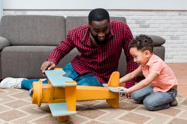 Zwarte vader en zoon spelen met speelgoed vliegtuig