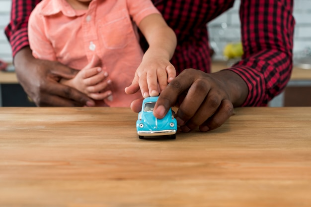 Zwarte vader en zoon spelen met speelgoedauto op tafel