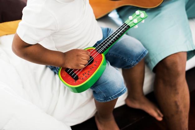 Zwarte vader geniet van gitaar spelen met zijn kind samen geluk