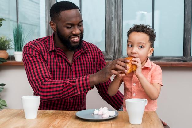 Zwarte vader voedende zoon met croissant