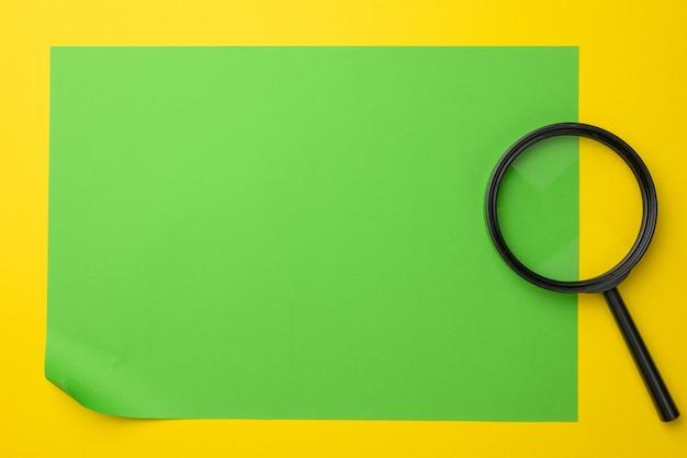 Zwarte vergrootglas op een geel oppervlak. het concept van onzekerheid en het zoeken naar oplossingen, twijfels, plat leggen