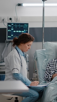 Zwarte verpleegster controleert de vitale functies van de patiënt die de hartslag controleert en vitamine injecteert in iv-vloeistoffen infuuszak op de ziekenhuisafdeling