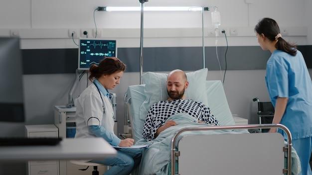 Zwarte verpleegster controleert de vitale functies van de patiënt die de hartslag controleert en vitamine injecteert