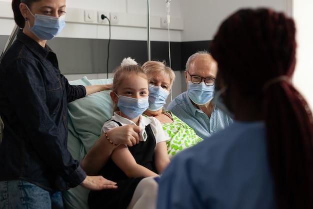Zwarte verpleegster die oudere patiënt controleert en ziektebehandeling uitlegt