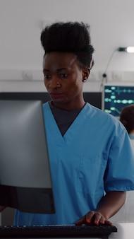 Zwarte verpleegster typt ziektesymptoom terwijl gespecialiseerde artsen de zieke vrouw controleren die gezondheidsbehandeling op klembord schrijft tijdens medische afspraak. patiënt rust in bed in ziekenhuisafdeling