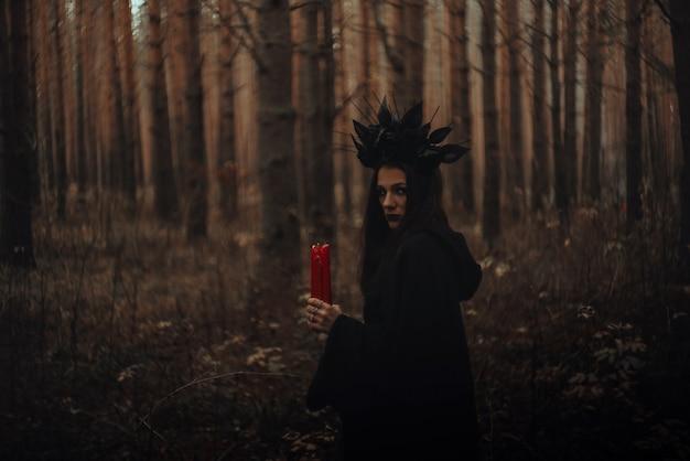 Zwarte verschrikkelijke heks houdt kaarsen in haar handen in een donker bos