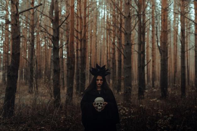 Zwarte verschrikkelijke heks met een schedel in de handen van een dode man in het bos