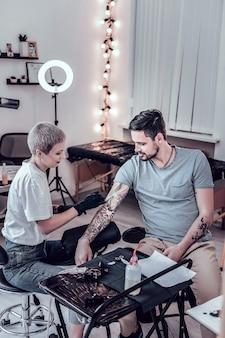 Zwarte verzadigde inkt. kortharige blonde vrouw die met tattoo sleeve aan de hand van haar cliënt werkt Premium Foto