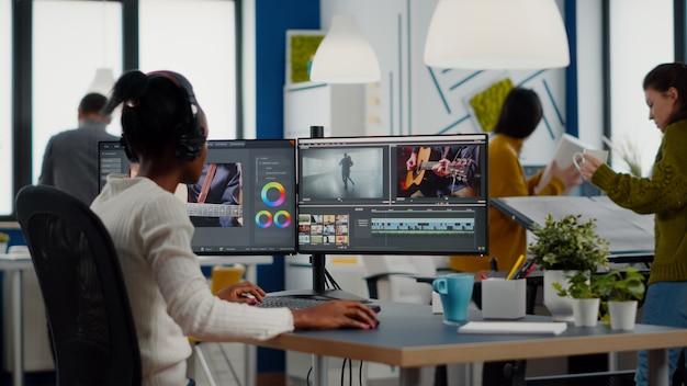 Zwarte videograaf zet headset op tijdens filmbewerking
