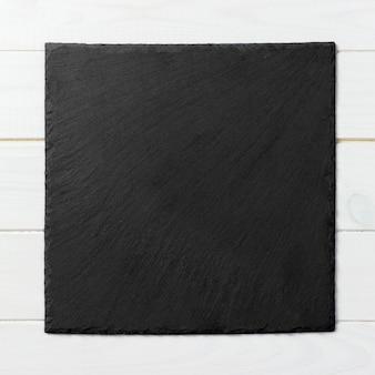 Zwarte vierkante plaat op houten achtergrond
