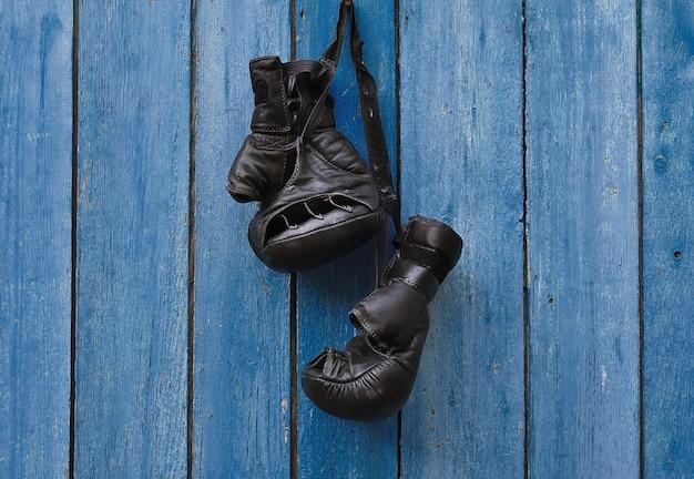 Zwarte vintage bokshandschoenen die op een oude roestige spijker hangen