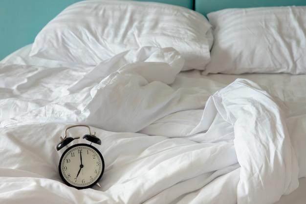 Zwarte vintage klok op wit bed.