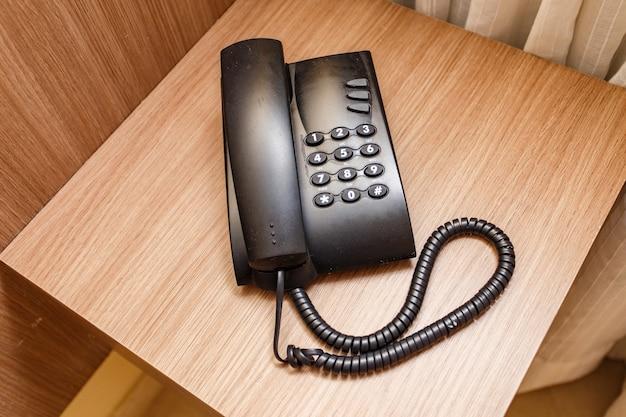 Zwarte vintage telefoon op een bruine tafel in het hotel.