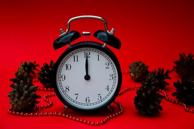 Zwarte vintage wekker geïsoleerd op een rode achtergrond met kerstversiering en kegels