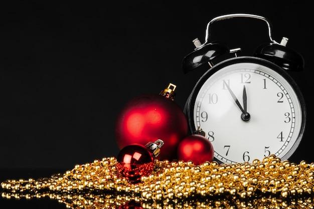 Zwarte vintage wekker met kerstballen en decor op donkere zwarte achtergrond