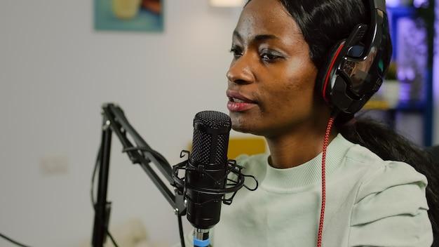 Zwarte vlogger in de lucht tijdens podcastkanaal met behulp van mixer die geluid en professionele microfoon controleert