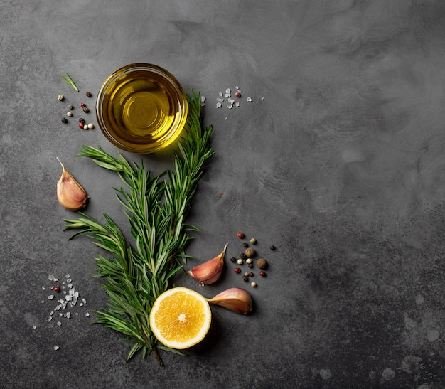 Zwarte voedselachtergrond met olijfolie, rozemarijn, citroen en kruiden. bovenaanzicht, kopie van de ruimte