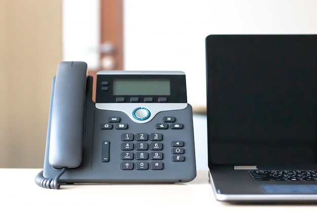 Zwarte voip-telefoon op bureau met computerlaptop