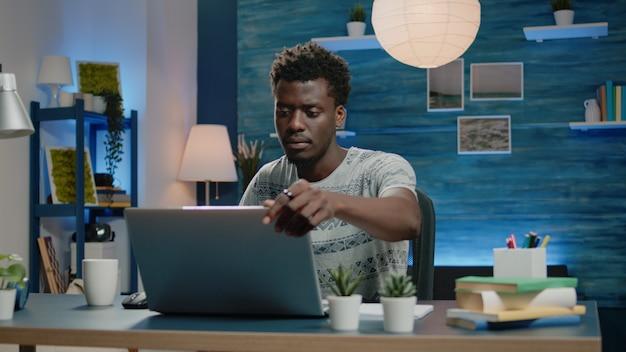 Zwarte volwassene die thuis werkt met laptop en koffie aan het bureau