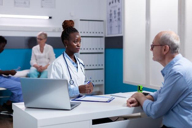 Zwarte volwassene met doktersberoep in gesprek met senior patiënt