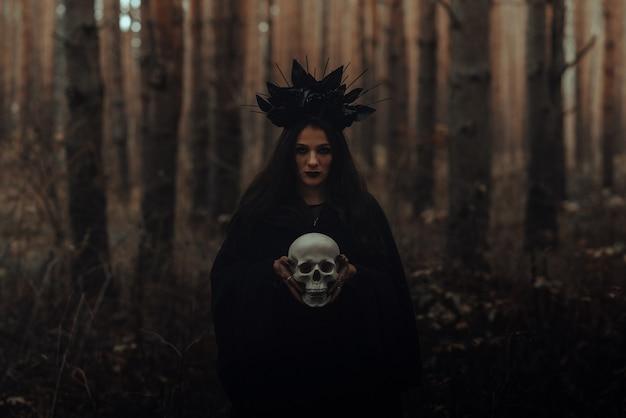 Zwarte vreselijke heks houdt de schedel van een dode man in haar handen in een donker bos