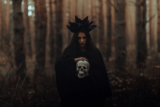 Zwarte vreselijke heks met een schedel in de handen van een dode man in het bos