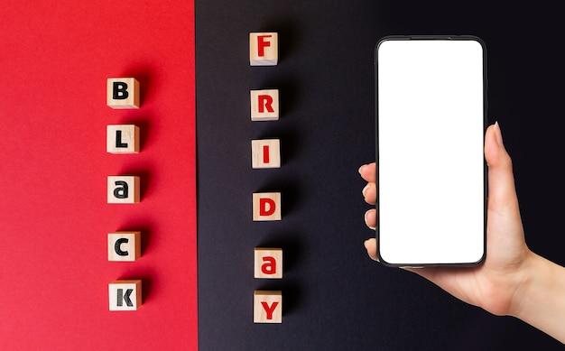 Zwarte vrijdag concept. houten kubussen met de inscriptie black friday. plat leggen. de hand van een vrouw houdt een smartphone vast.