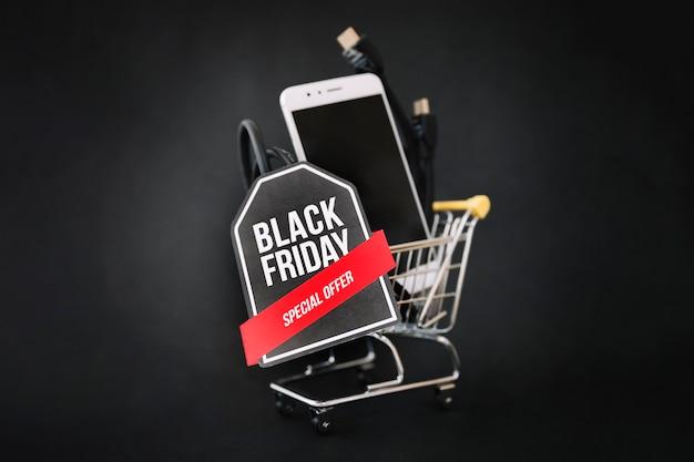 Zwarte vrijdag decoratie met smartphone in winkelwagen en label
