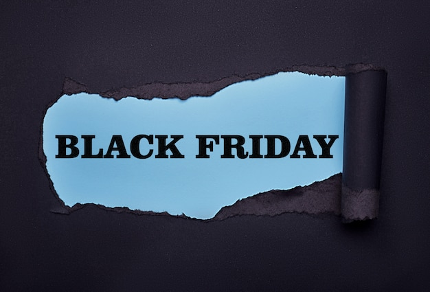 Zwarte vrijdag. gat in het zwarte papier. gescheurd. blauw papier samenvatting