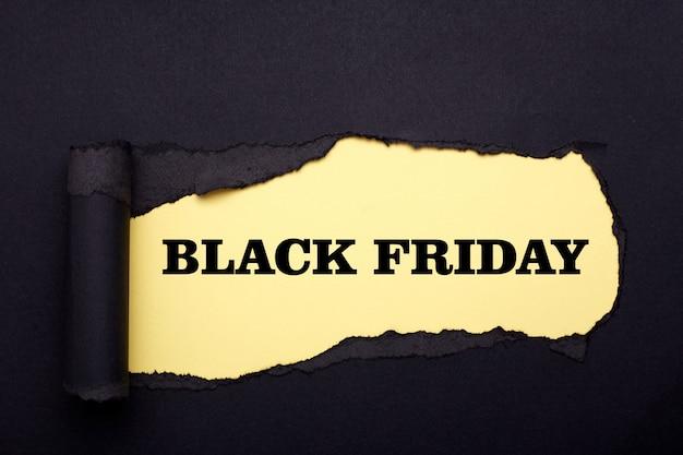 Zwarte vrijdag. gat in het zwarte papier. gescheurd. geel papier. samenvatting