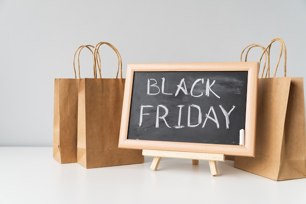 Zwarte vrijdag geschreven op bord met boodschappentassen