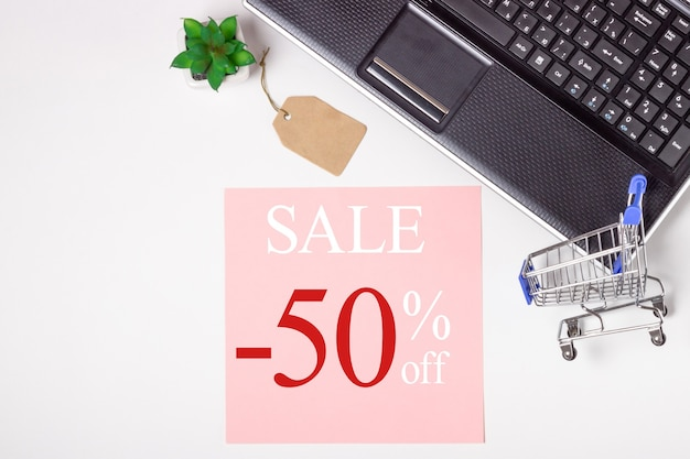 Zwarte vrijdag. laptop, nota boek en winkelwagentje op een witte achtergrond